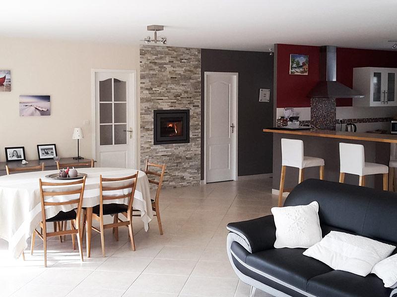 Insert noir encastré dans mur en pierre de parement beige entre cuisine et salle à mangerdans pièce de vie