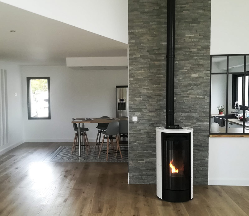 Poêle design cylindrique noir et blanc dans pièce de vie maison récente