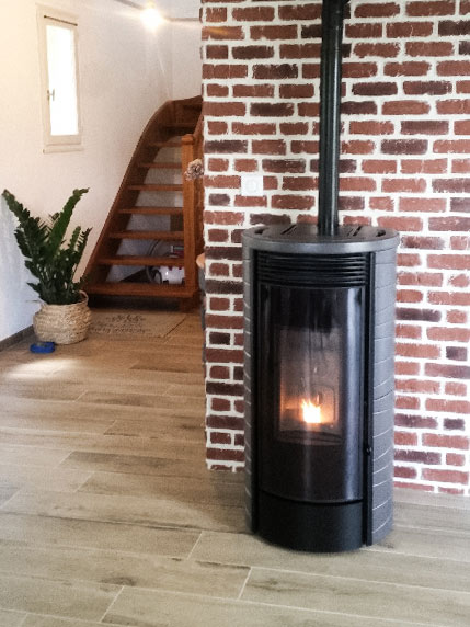 Poêle design noir et gris posé contre mur de brique rouge AquaFeu